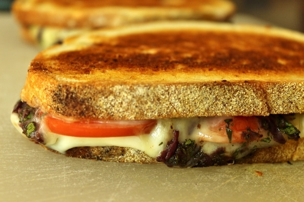 a side view of a grilled cheese sandwich with tomatoes and olive tapenade