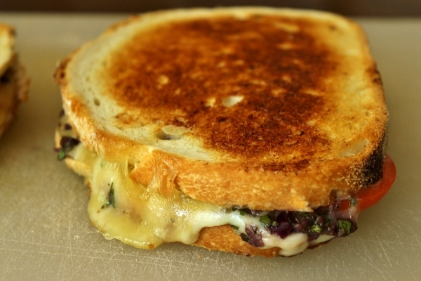 A close up of a grilled cheese sandwich with olive tapenade