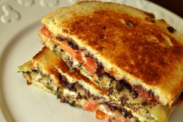 an overhead view of a halved grilled cheese with tomatoes and olive tapenade inside