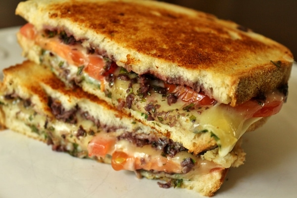 stacked grilled cheese sandwich halves with olive tapenade and sliced tomatoes