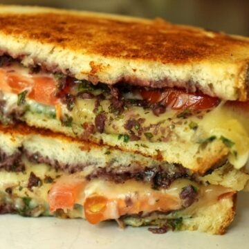 A close up of a cross section of a grilled cheese with kalamata tapenade