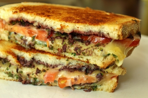 closeup of a halved grilled cheese with tomatoes, olive tapenade, and pesto