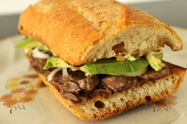 a side view of a Mexican steak sandwich on a baguette segment