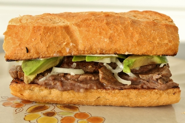 a Mexican steak sandwich with refried black beans, sliced onions and avocado