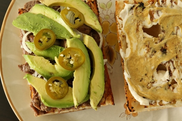 assembling a sandwich with steak, avocado, jalapenos, mustard and mayonnaise