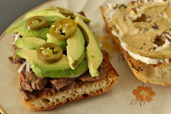a closeup of a half assembled pepito sandwich with steak and avocado