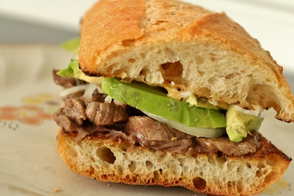 a closeup of a Mexican steak sandwich (pepito) with onions and avocado