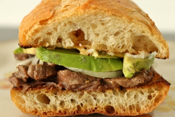 a side view of a pepito (Mexican steak sandwich) with avocado
