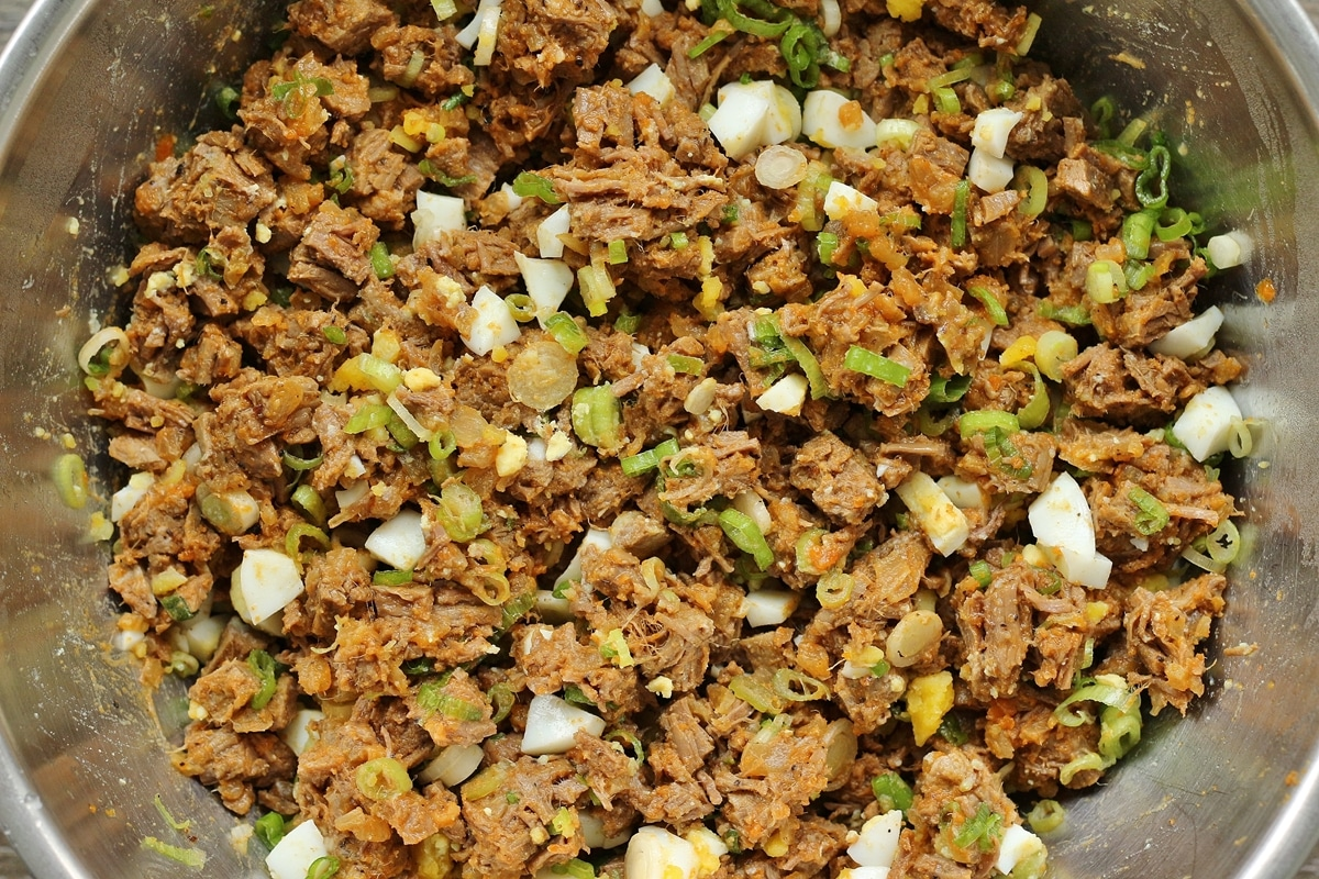 chopped beef with hard-boiled eggs and scallions in a metal mixing bowl