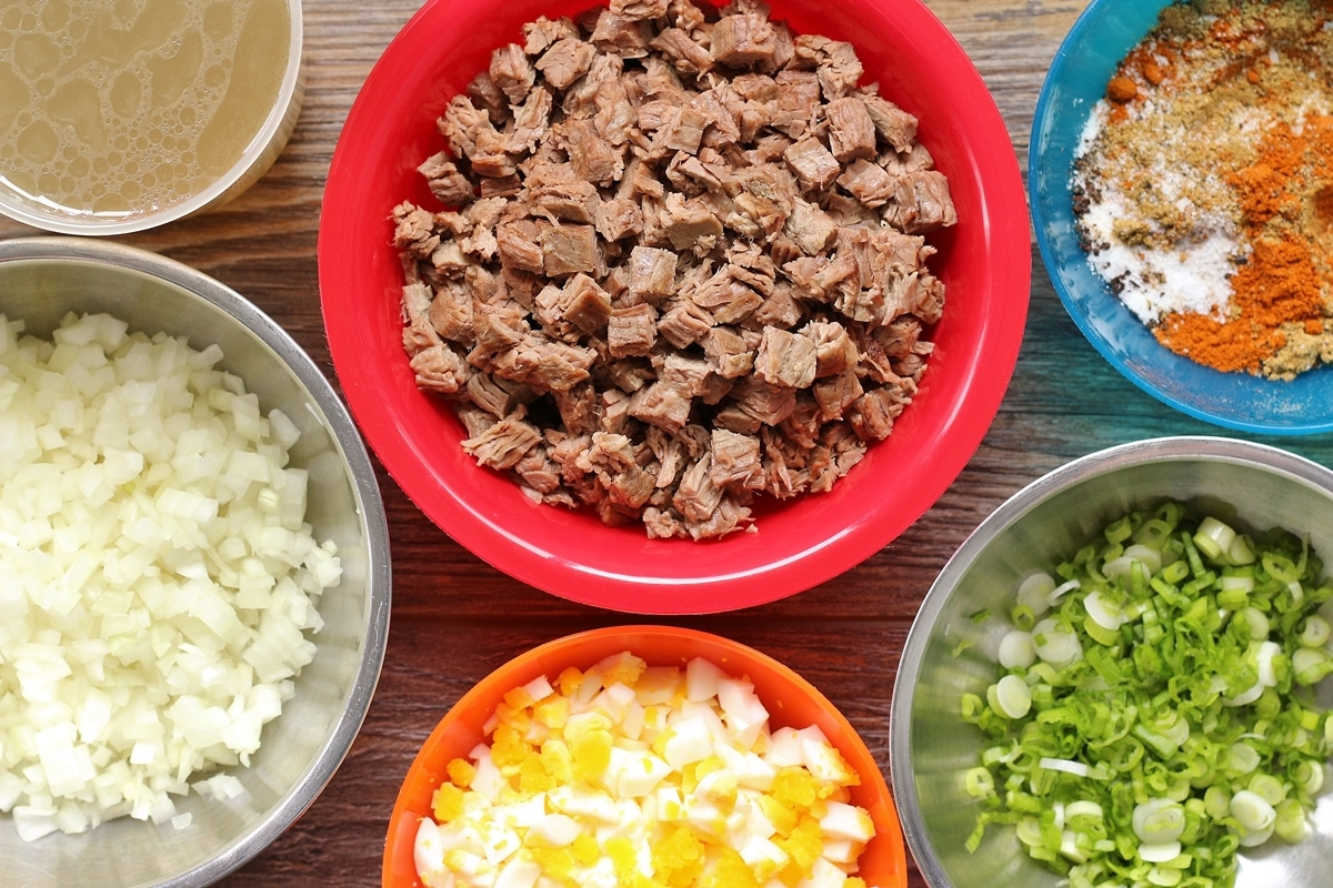 various empanada filling ingredients in colorful bowls