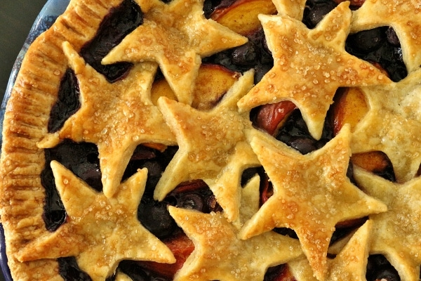 overhead view of a blueberry nectarine pie with star decorations on top
