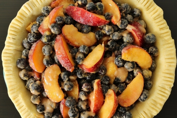 overhead view of an unbaked pie crust filled with blueberry nectarine filling