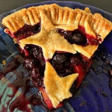 overhead view of a slice of blueberry nectarine pie with star decorations