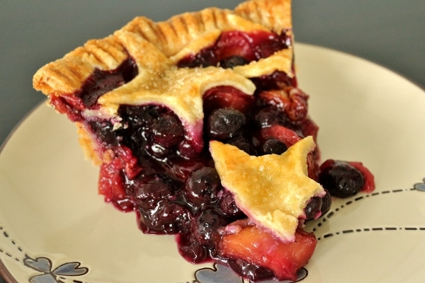 a slice of juicy blueberry nectarine pie on a plate