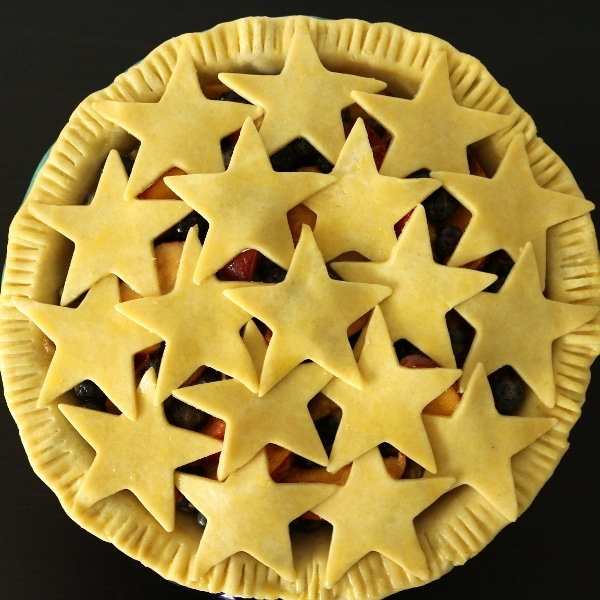an unbaked blueberry nectarine pie with star cutouts on top