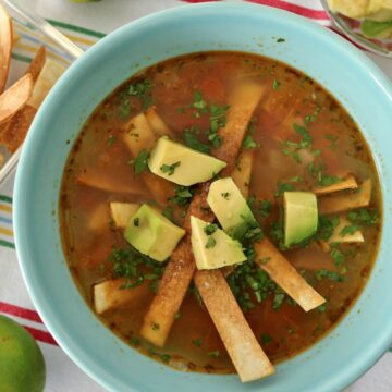 Soup topped with cubed avocado and fried tortilla strips in a blue bowl.