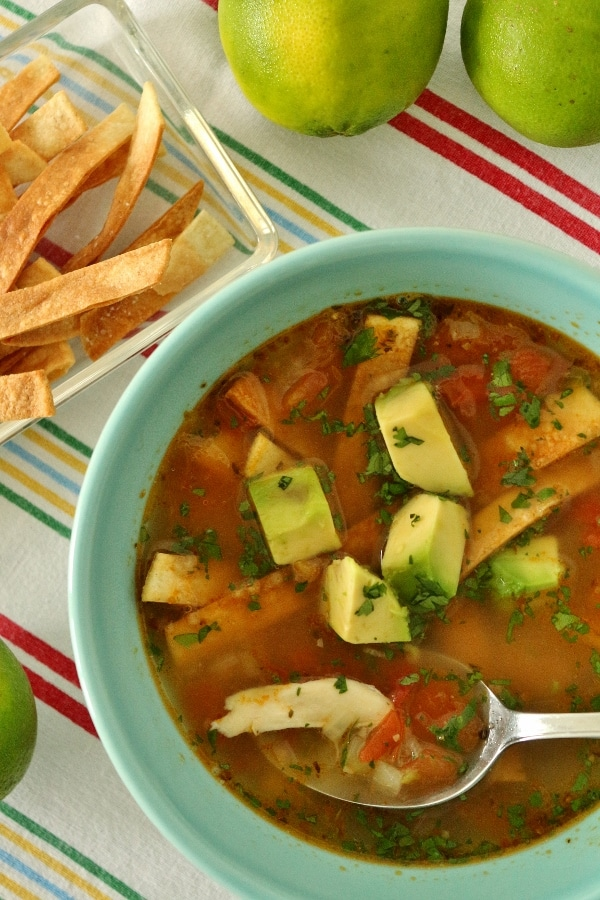 closeup of a bowl of chicken soup with tortilla strips and chopped avocado