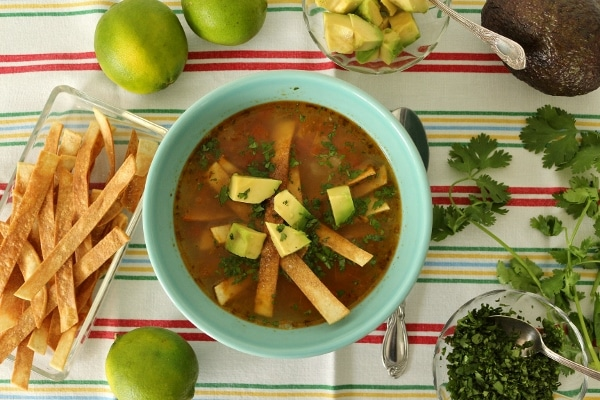 overhead view of a sopa de lima in a blue bowl, surrounded by garnishes