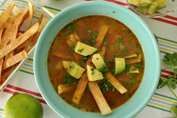 overhead view of a bowl of Sopa de Lima garnished with tortilla strips and avocado