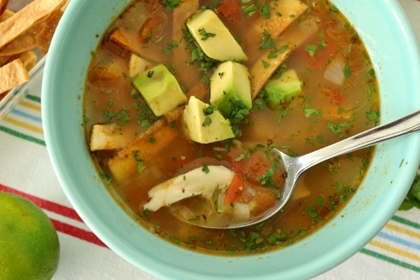 a spoon scooping up some chicken in a bowl of Yucatan-style lime soup