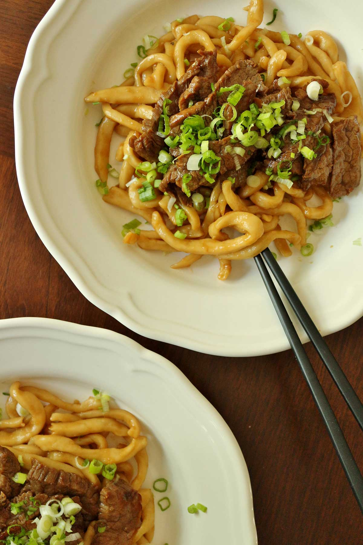 Two white plates with udon noodles topped with teriyaki beef and scallions.