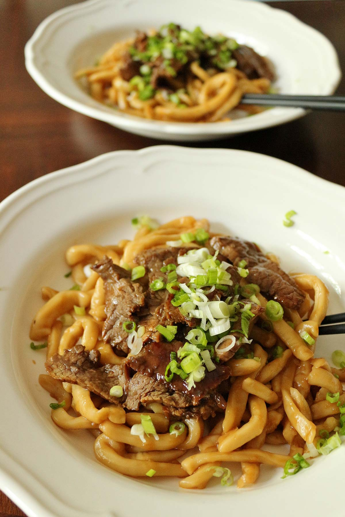 Two white plates with stir-fried udon noodles topped with sliced teriyaki beef and scallions.