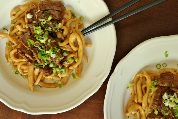 overhead view of 2 plates of udon noodles with beef and scallions