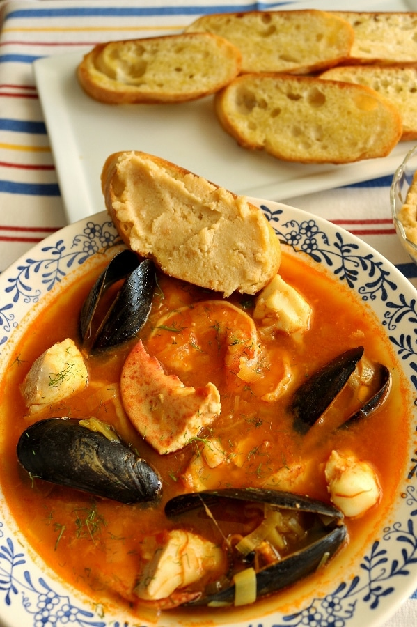 a bowl of bouillabaise seafood stew with mussels, fish, and lobster