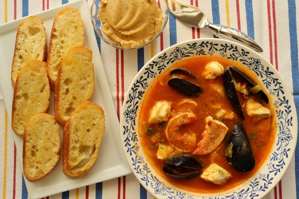 overhead view of a bowl of seafood stew with baguette toasts and a garlicky spread