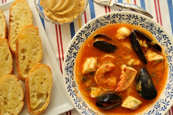 overhead view of a shallow bowl of Provencal fish stew with baguette crisps on the side