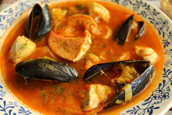 a closeup of a bowl of bouillabaise with mussels, fish, and lobster