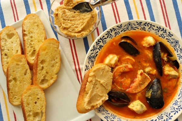 overhead view of a bowl of bouillabaise with croutons and rouille on the side