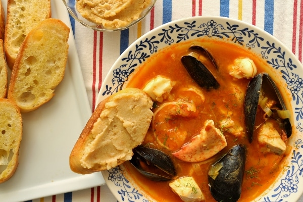 overhead closeup of a bowl of Provencal fish stew with garlic toasts