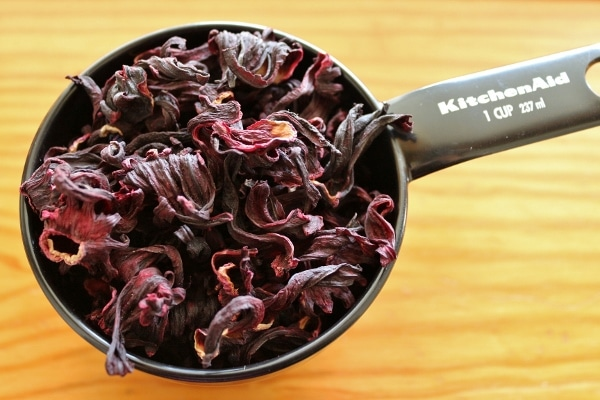 dried hibiscus flowers in a black measuring cup