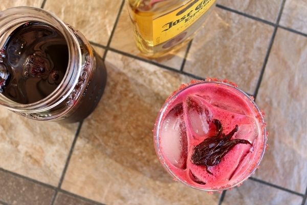overhead view of a pink hibiscus margarita, a bottle of tequila, and hibiscus syrup