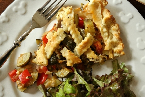 overhead view of a slice of ratatouille pie with salad