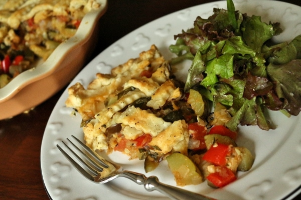 a slice of ratatouille pie with salad on a white plate
