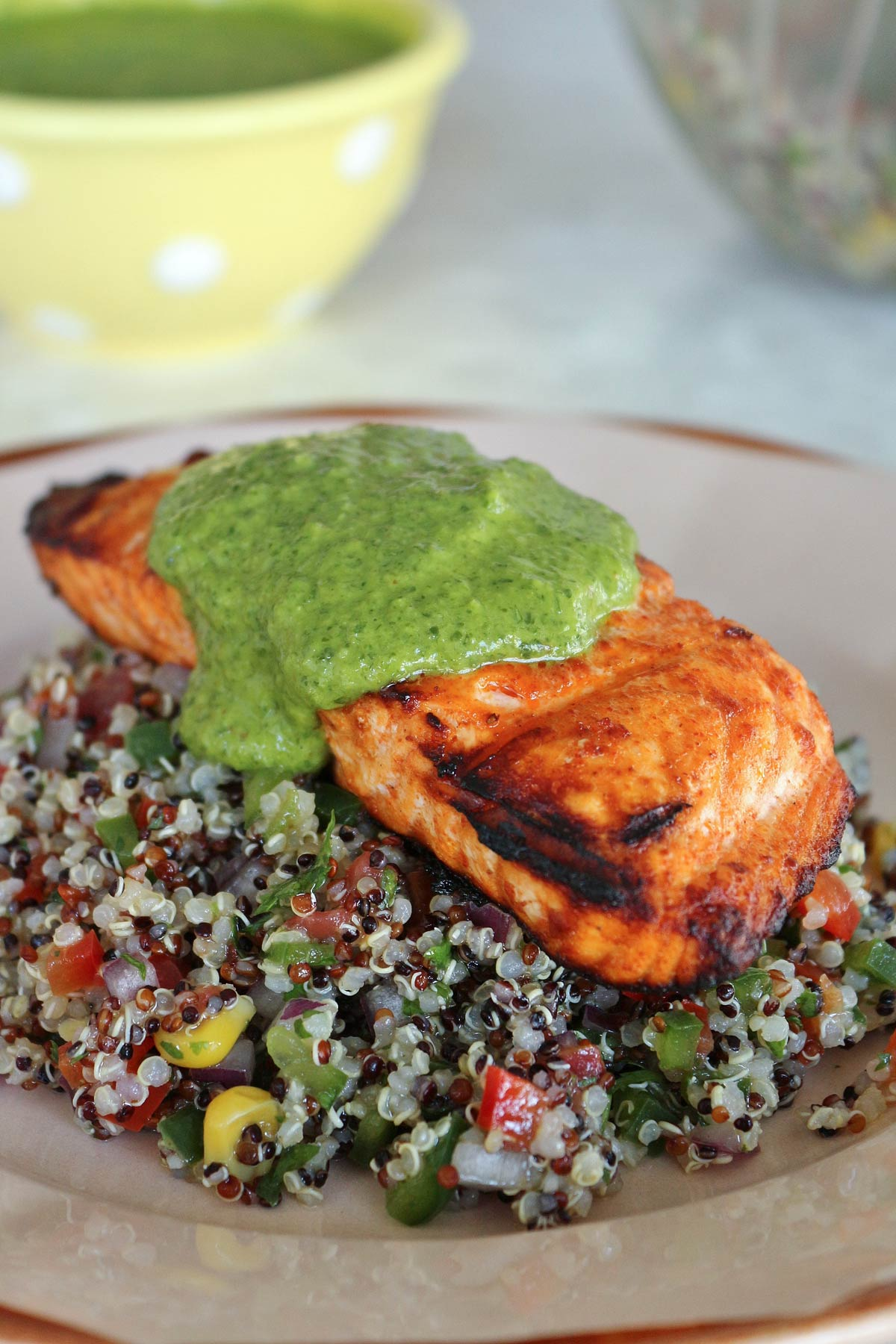 A grilled salmon fillet on a bed of quinoa salad topped with bright green sauce.