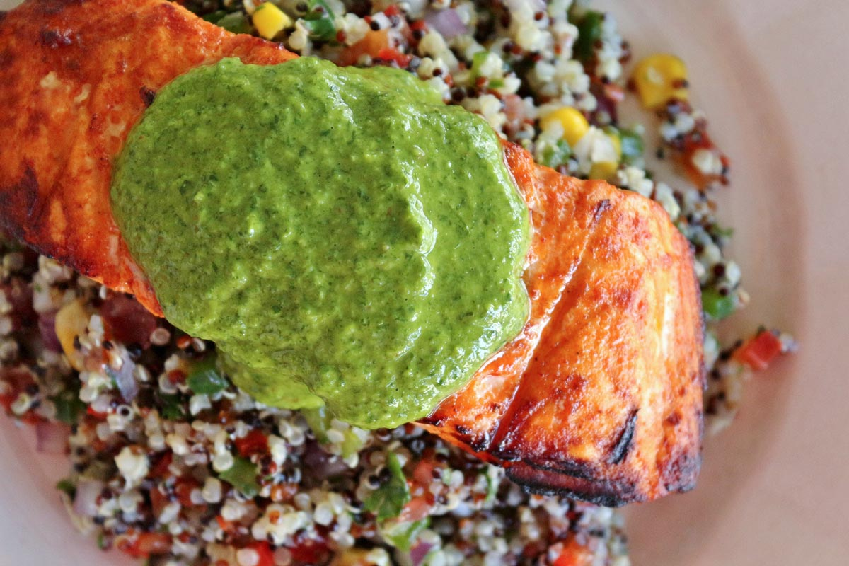 Closeup of a pool of bright green arugula chimichurri on top of a grilled salmon fillet.