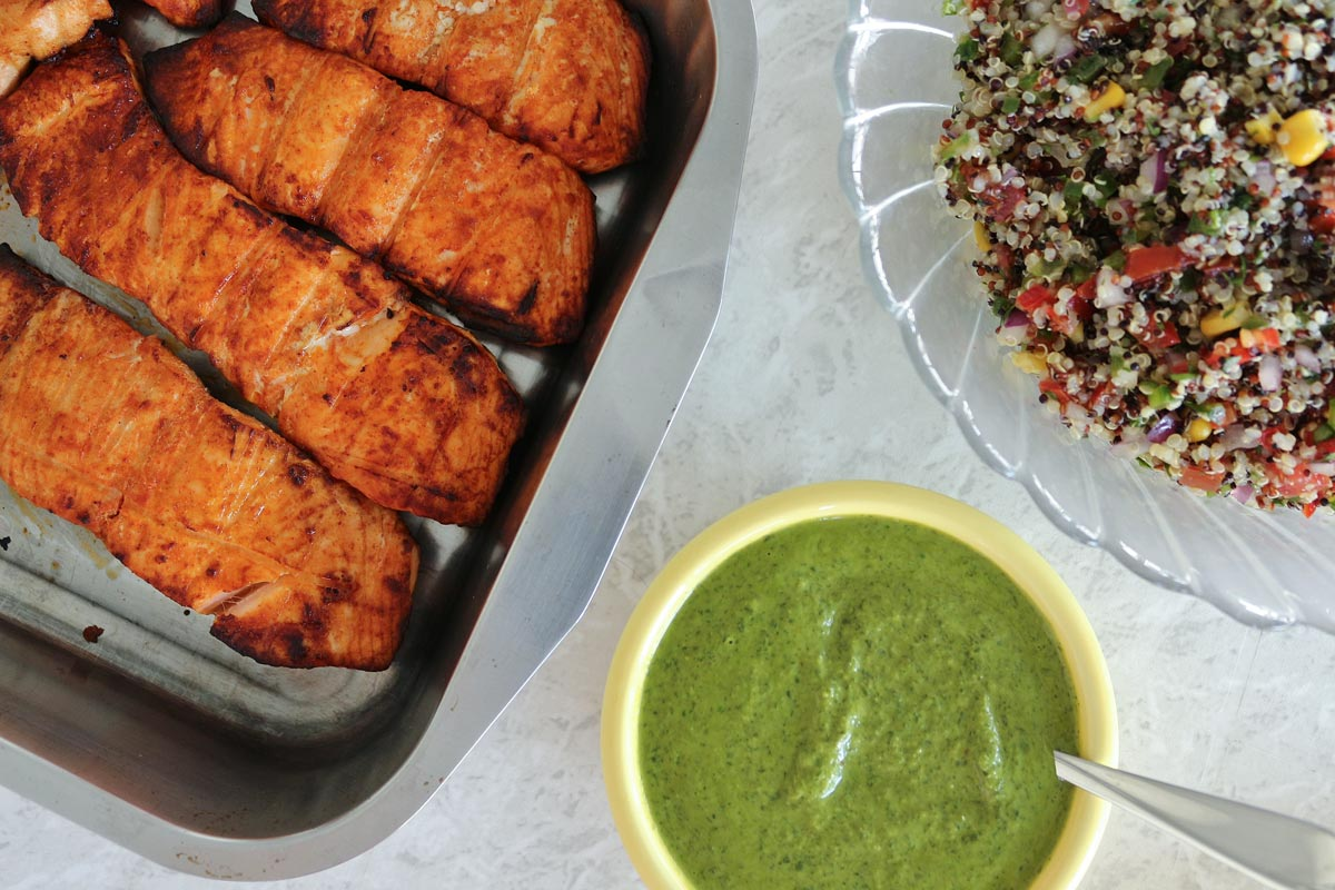 Grilled salmon fillets in a metal pan, bowls of quinoa salad and arugula chimichurri.