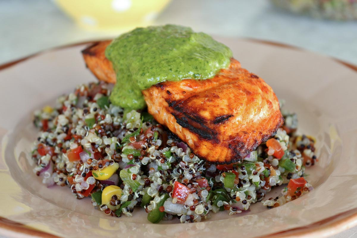 Grilled salmon over quinoa salad, topped with green sauce on an antique plate.