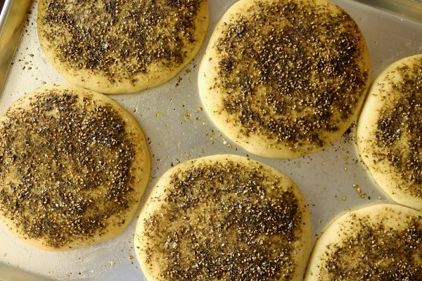 an overhead view of loaves of bread topped with za\'atar spice mixture