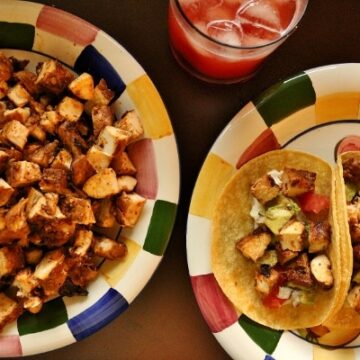 chicken tacos on a colorful plate, a platter of cubed chicken and a strawberry drink