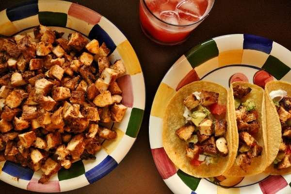 Three chicken adobo tacos on a plate with cubes of chicken, tomato, and guacamole. There is a glass of strawberry agua fresca in the background and a platter of cubed adobo chicken.