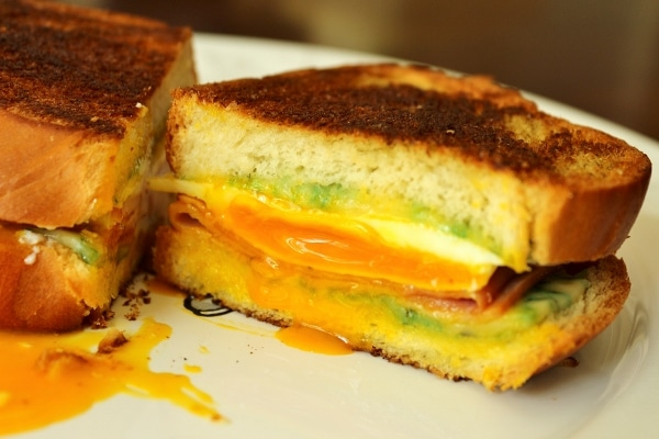 a halved breakfast grilled cheese sandwich with runny egg