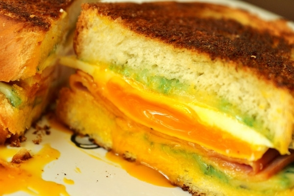 a closeup of a cross section of a ham, egg, and grilled cheese sandwich