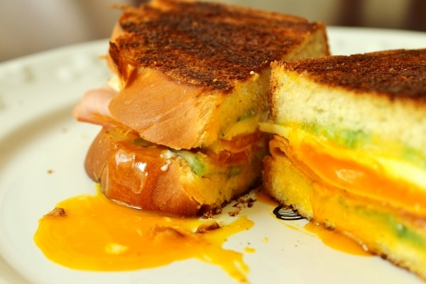closeup of a halved breakfast sandwich with runny egg yolk