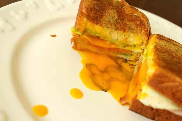 a halved breakfast sandwich with runny egg yolk on the plate