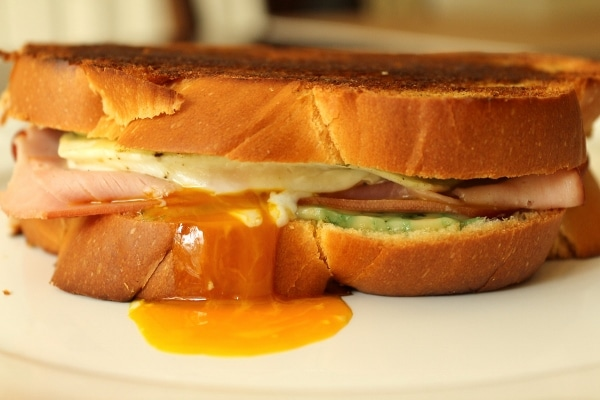 a close up of a grilled cheese sandwich with a fried egg and ham