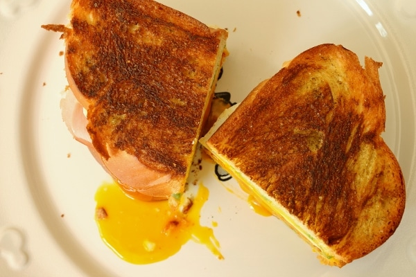 overhead view of a halved breakfast grilled cheese with runny egg yolk on the plate